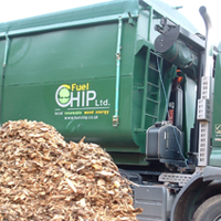 A pile of woodchip next to the Practicality Brown biomass fuel wagon